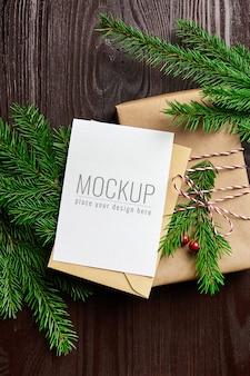 Kerst wenskaart mockup met versierde geschenkdoos en dennentakken