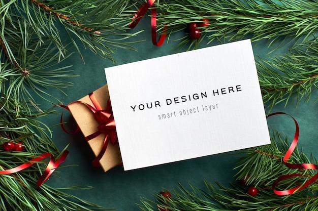 Kerst wenskaart mockup met versierde geschenkdoos en pijnboomtakken