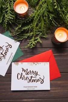 Kerstbrieven en wenskaarten liggen op bruin houten tafel met dennentakken en kaarsen mockup