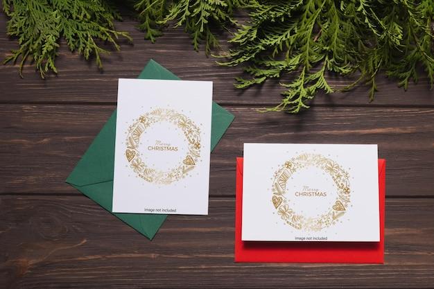 Kerstbrieven met wenskaarten liggen op een bruin houten tafel met dennentakken en kaarsen.