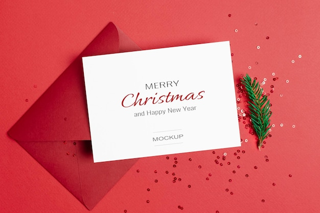 Kerstgroet of uitnodigingskaartmodel met envelop en feestelijke confetti-versieringen op rood