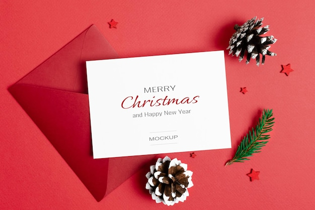 Kerstgroet of uitnodigingskaartmodel met envelop en kegelsversieringen op rood