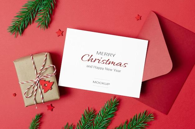 Kerstkaartmodel met envelop en versierde geschenkdoos met dennentakken op rood