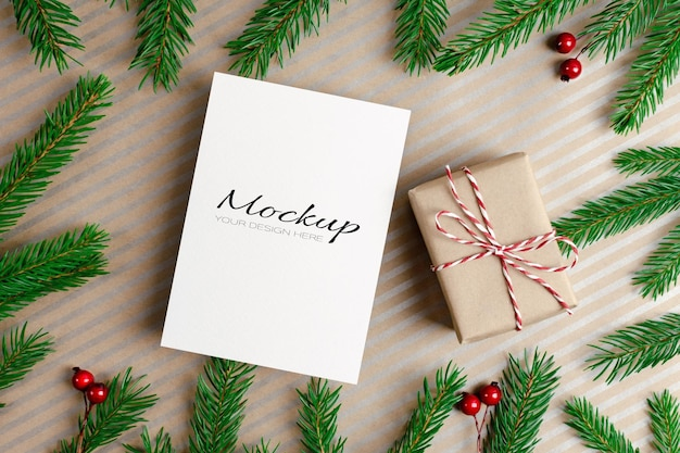 Kerstkaartmodel met geschenkdoos en groene dennenboomtakken
