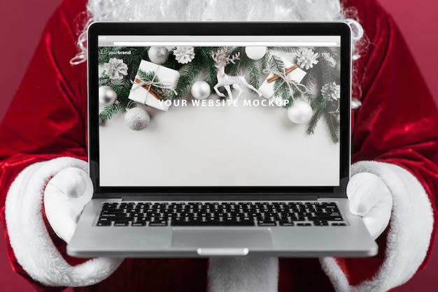 Kerstman die laptop mockup voorstelt