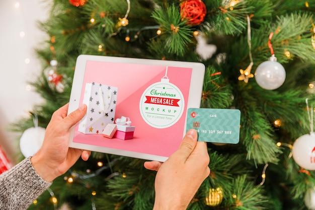 Kerstmis verkoop mockup met vrouw met behulp van tablet pc