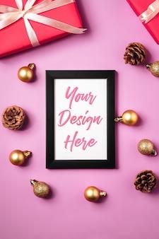 Kerstmissamenstelling met leeg afbeeldingsframe, gouden kerstballen, geschenkdozen en dennenappels