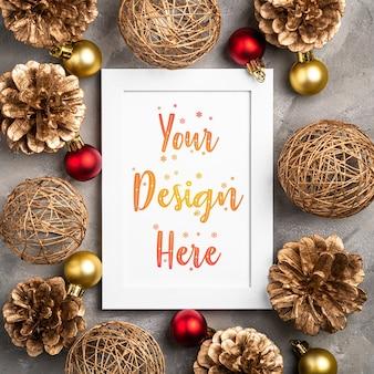 Kerstmissamenstelling met leeg afbeeldingsframe met gouden ornamenten en denneappels