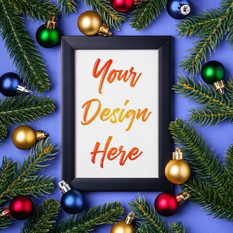 Kerstmissamenstelling met leeg afbeeldingsframe met kleurrijke ornamenten en dennentakken