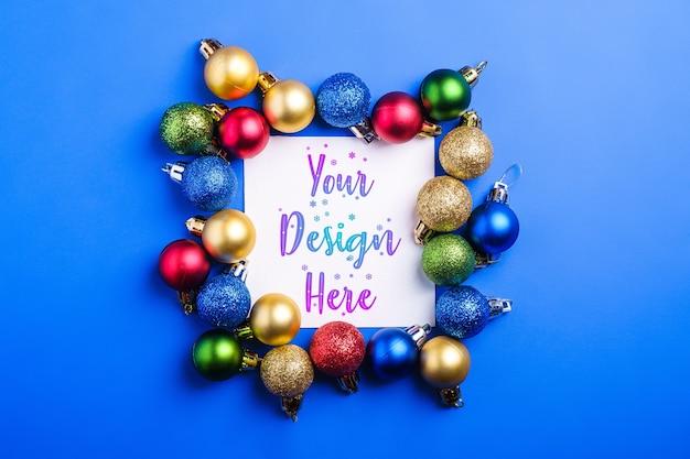Kerstmissamenstelling met witte vierkante kaart en kleurrijke snuisterijen
