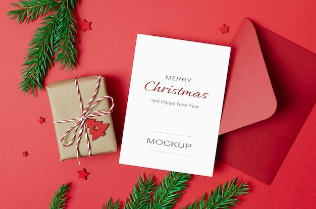 Kerstwenskaartmodel met envelop en versierde geschenkdoos op rood