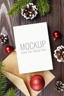 Kerstwenskaartmodel met feestelijke decoraties, kegels en dennentakken