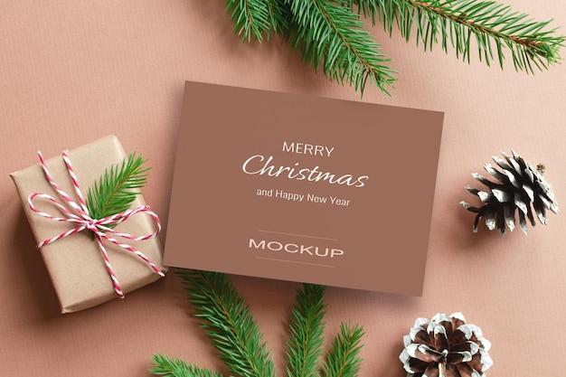 Kerstwenskaartmodel met geschenkdoos en dennenboomtakken met kegels