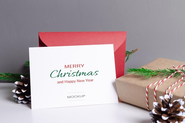 Kerstwenskaartmodel met rode envelop en versierde geschenkdoos met dennenappels