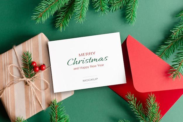 Kerstwenskaartmodel met rode envelop, geschenkdoos en groene dennenboomtakken