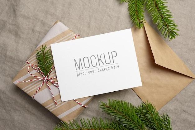 Kerstwenskaartmodel met versierde geschenkdoos, envelop en dennenboomtak op linnen achtergrond