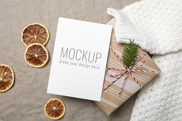 Kerstwenskaartmodel met versierde geschenkdoos, gebreide trui en droge sinaasappels
