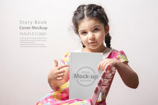 Klein meisje wijzend op een verhalenboek met blanco omslag zit op een stoel