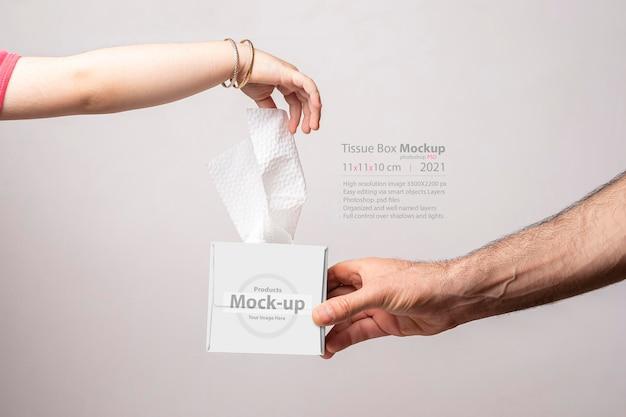 Kleine meisjeshand die een tissue uit een tissuedoos trekt