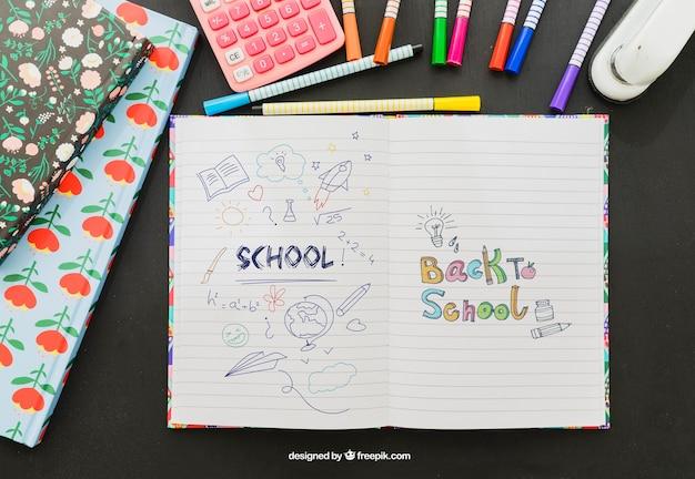 Kleurrijke tekening op het notitieboekje met schoolmateriaal