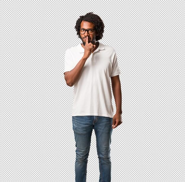 Knappe afrikaanse amerikaan die een geheim houden of om stilte, ernstig gezicht, gehoorzaamheidconcept vragen