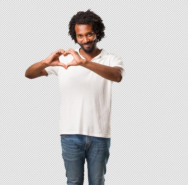 Knappe afrikaanse amerikaan die een hart met handen maakt, de liefde en de vriendschap uitdrukt, gelukkig en glimlachend