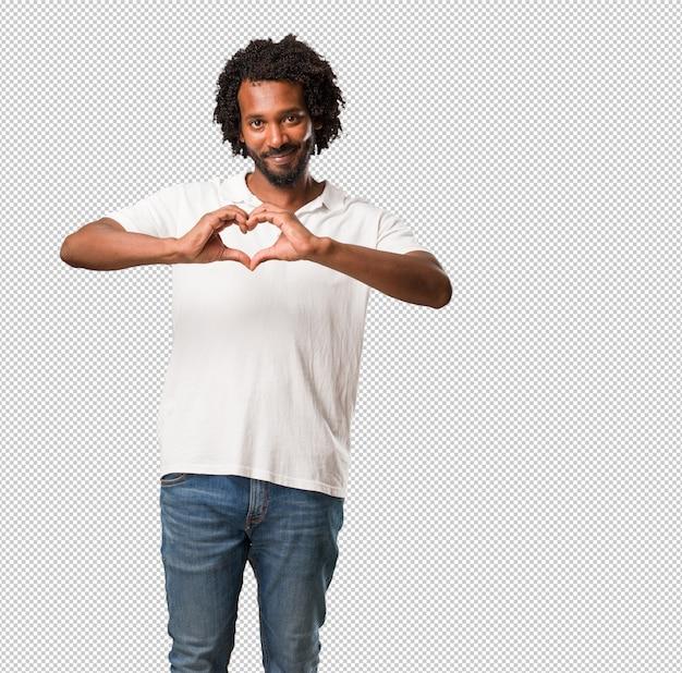 Knappe afrikaanse amerikaan die een hart met handen maakt, het concept liefde en vriendschap uitdrukt, gelukkig en glimlachend