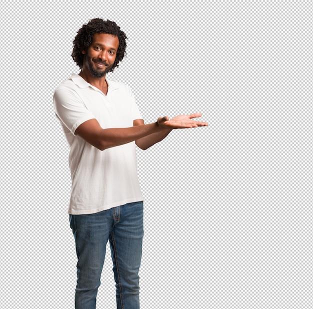 Knappe afrikaanse amerikaan die iets met handen houden, een product tonen, glimlachend en vrolijk, die een denkbeeldig voorwerp aanbieden
