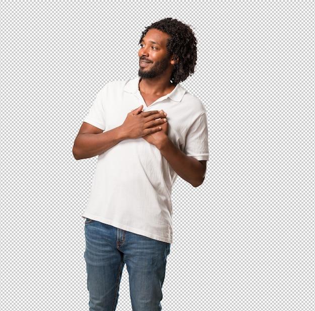 Knappe afro-amerikaan doet een romantisch gebaar, verliefd op iemand of toont genegenheid voor een vriend