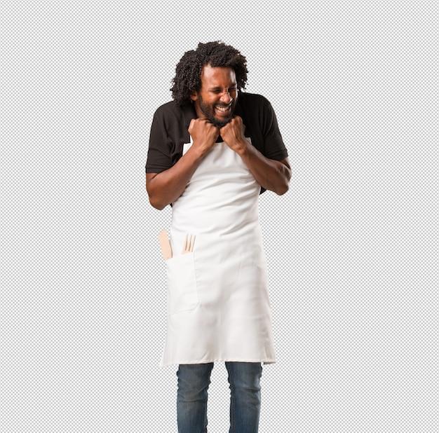 Knappe afro-amerikaanse bakker, heel blij en opgewonden, hij hief zijn armen op, vierde een overwinning of succes en won de loterij