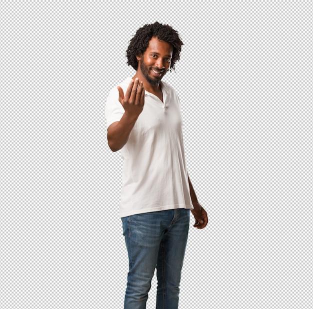 Knappe afro-amerikaanse uitnodigend om te komen, zelfverzekerd en glimlachend een gebaar met de hand maken, positief en vriendelijk zijn