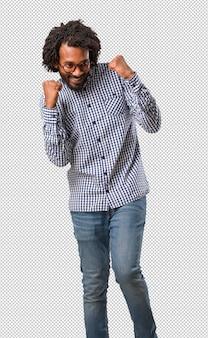 Knappe afro-amerikaanse zakenman erg blij en opgewonden, het verhogen van wapens, het vieren van een overwinning of een succes