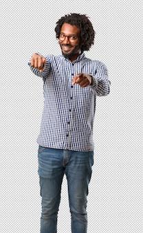 Knappe afro-amerikaanse zakenman vrolijk en glimlachen wijzend naar de voorkant