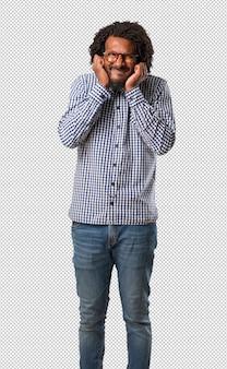 Knappe bedrijfs afrikaanse amerikaanse mens die oren behandelen met handen, boos en moe van het horen van wat geluid