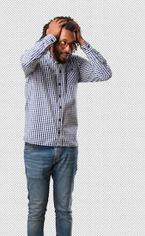 Knappe bedrijfs afrikaanse amerikaanse mens gefrustreerd en wanhopig, boos en droevig met handen op hoofd