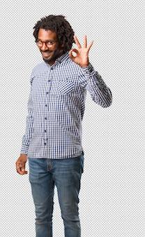 Knappe bedrijfs afrikaanse amerikaanse mens vrolijk en zeker doen ok gebaar, opgewekt en gillend, concept goedkeuring en succes