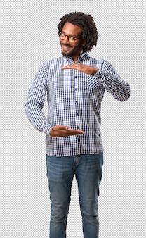 Knappe bedrijfs afrikaanse amerikaanse mensenholding iets met handen, die een product tonen, glimlachend en vrolijk, die een denkbeeldig voorwerp aanbieden