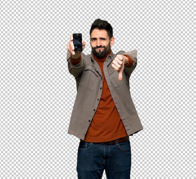 Knappe man met baard met verontruste gebroken smartphone houden