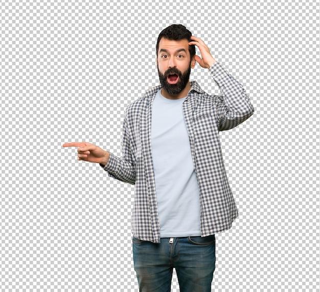 Knappe man met baard verrast en wijzende vinger aan de zijkant