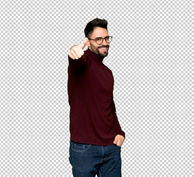Knappe man met een bril geven een thumbs up gebaar omdat er iets goeds is gebeurd