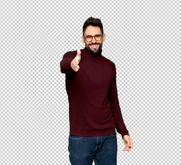 Knappe man met een bril handen schudden voor het sluiten van een goede deal