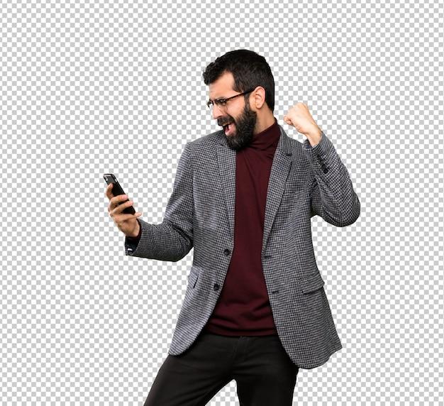 Knappe man met een bril met telefoon in de overwinningspositie