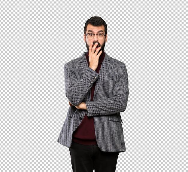 Knappe man met een bril verrast en geschokt tijdens het kijken naar rechts