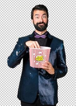 Knappe man met pailletten jasje eten popcorns