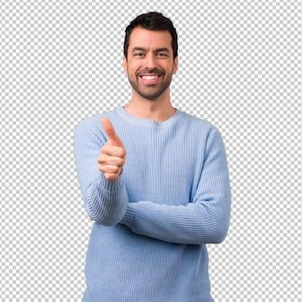 Knappe mens die duimen op gebaar en het glimlachen geeft