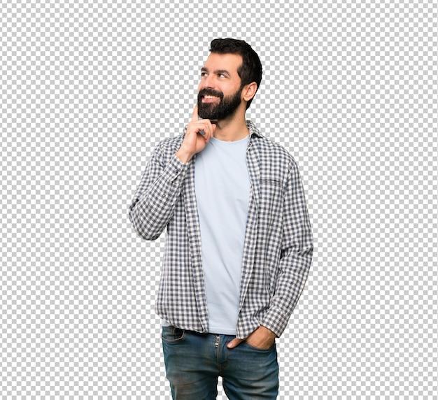 Knappe mens die met baard een idee denkt terwijl omhoog het kijken