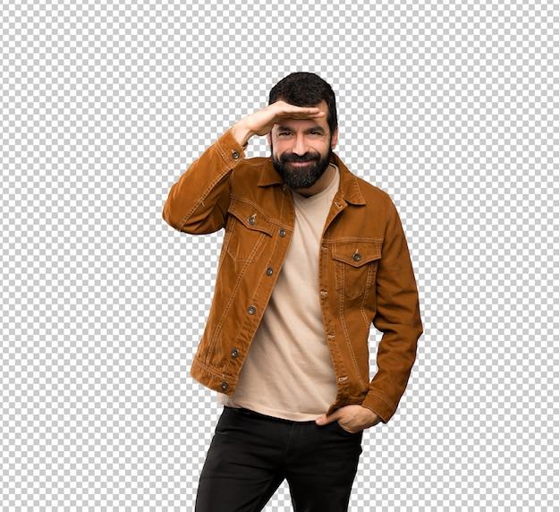 Knappe mens die met baard ver weg met hand kijken om iets te kijken