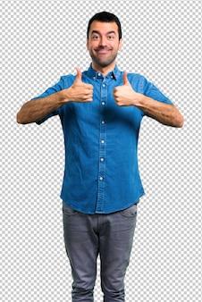 Knappe mens met blauw overhemd die duimen op gebaar en het glimlachen geven