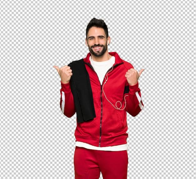 Knappe sportman die duimen op gebaar met beide handen en het glimlachen geeft