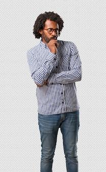 Knappe zakelijke afro-amerikaanse man twijfelen en verward, denken aan een idee of bezorgd over iets
